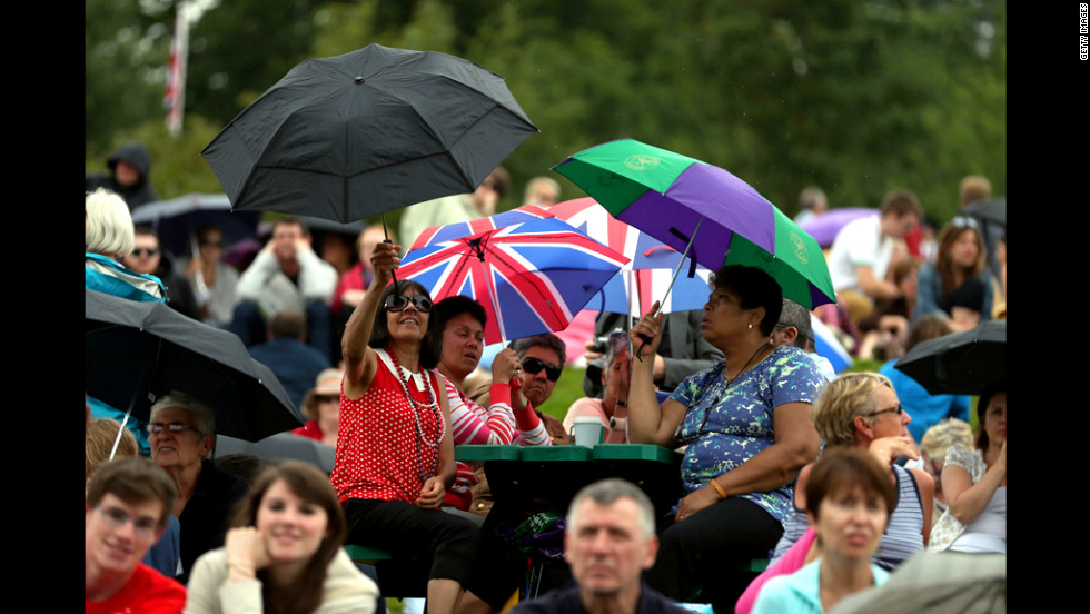 The crowd takes shelter from showers on day three of Wimbledon.