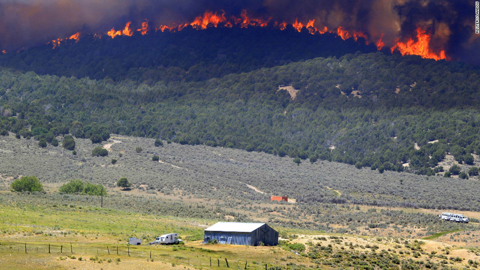 A wall of fire makes its way down a hillside toward a farm north of Fairview, Utah, on Tuesday, June 26. The Wood Hollow Fire, one of at least three wildfires burning in Utah, has grown to nearly 39,000 acres.
