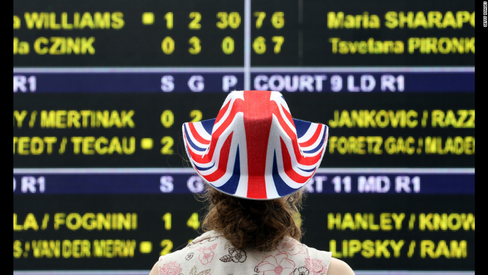 A fan studies the scoreboard at the Wimbledon championships at the All England Lawn Tennis Club in London June 28