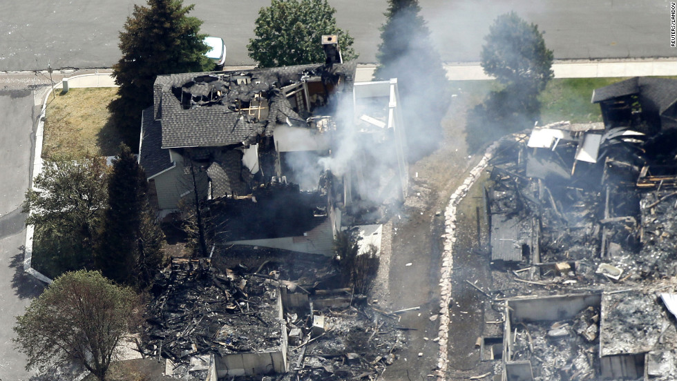 A partially burned home smolders Thursday in Colorado Springs.