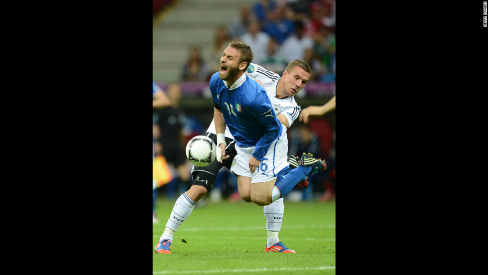 Italian midfielder Daniele De Rossi goes airborne past German forward Lukas Podolski on Thursday.