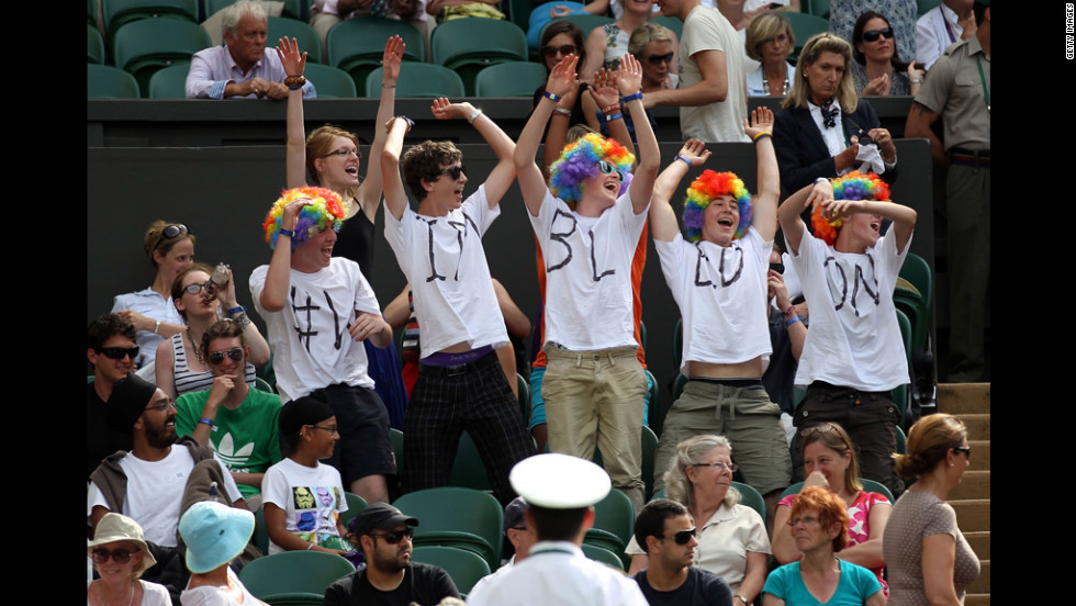 Tennis spectators cheer in colorful wigs June 28.