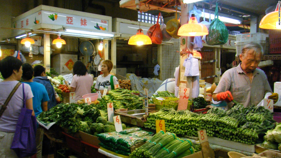 In Sai Ying Pun wet market stall holders compete for business, selling vegetables mostly imported from China. It's just a few blocks away from the central business district on Hong Kong Island.