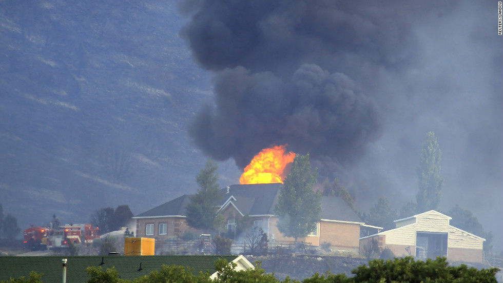 A house is engulfed in flames as fire crews fight to contain it at the Rose Crest fire in Herriman, Utah, on Friday, June 29. Crews are fighting to contain six separate blazes in the state.