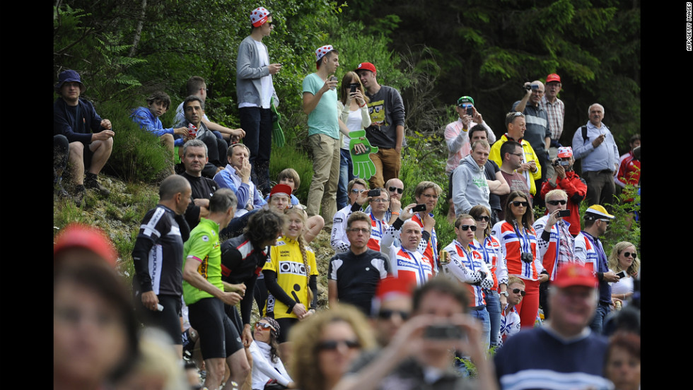 Fans wait on the roadside for the almost 200 riders to pass during Stage 1 on Sunday.