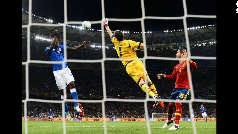 Iker Casillas of Spain, center, stretches for the ball in front of teammate Sergio Ramos, right, as Mario Balotelli of Italy attempts a goal on Sunday.