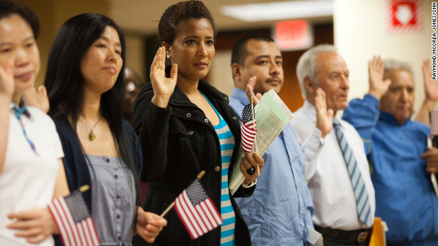 Immigrants take the Oath of Allegiance during a naturalization ceremony in Atlanta to officially become U.S. citizens.