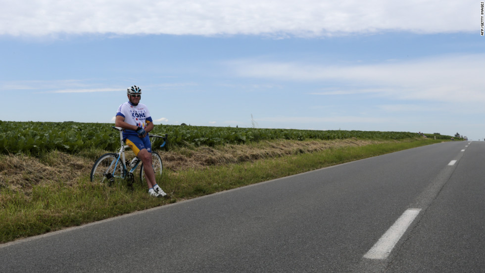 A spectator sits along the course Monday in Belgium, where Stage 2 of the race covers 129 miles from Vise to Tournai and is relatively flat.