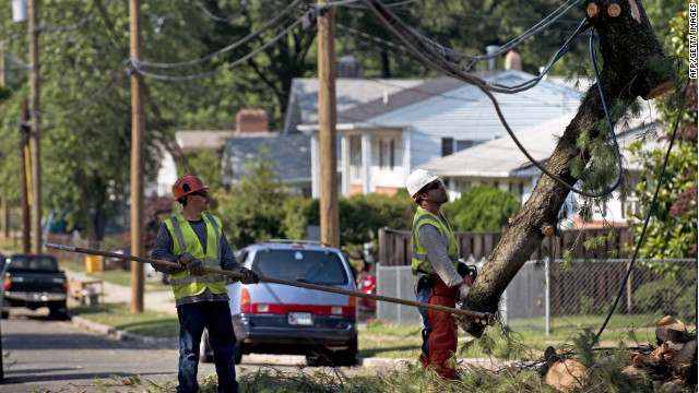Workers remove parts of a fallen tree from a telephone line in Maryland on Sunday.