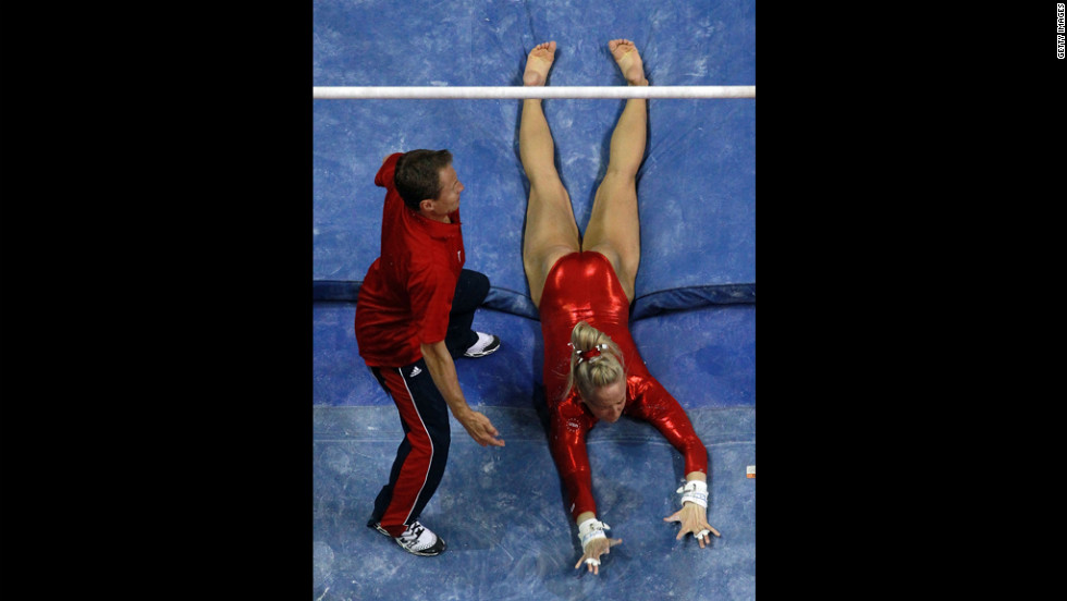 Nastia Liukin falls off the uneven bars in front of coach and dad Valeri Liukin during Day Four of the 2012 U.S. Olympic Gymnastics Team Trials.