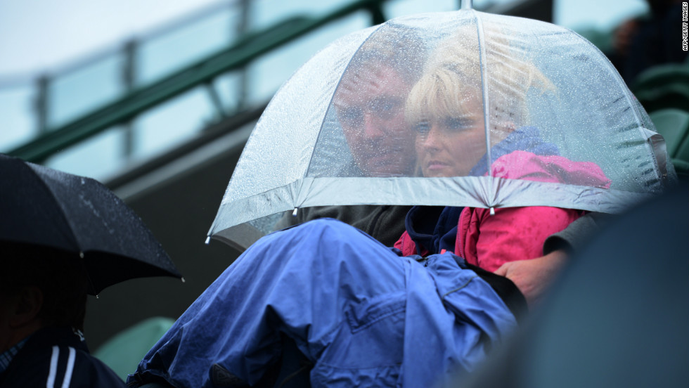 Spectators find shelter under an umbrella as they watch a match Monday.
