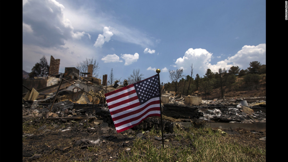An American flag waves Monday in front of a house leveled by the Waldo Canyon Fire in Colorado Springs. Residents began returnning to the area on Sunday after the fire forced thousands of people from their homes.