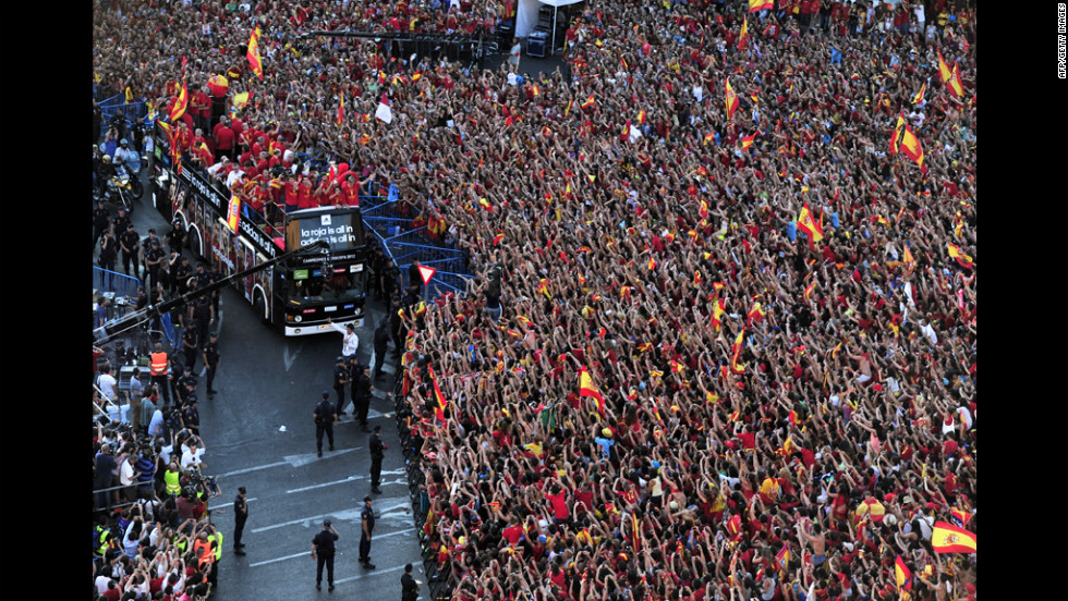 Spain's team arrives at Cibeles Square on top of a double-decker bus Monday after parading through Madrid.