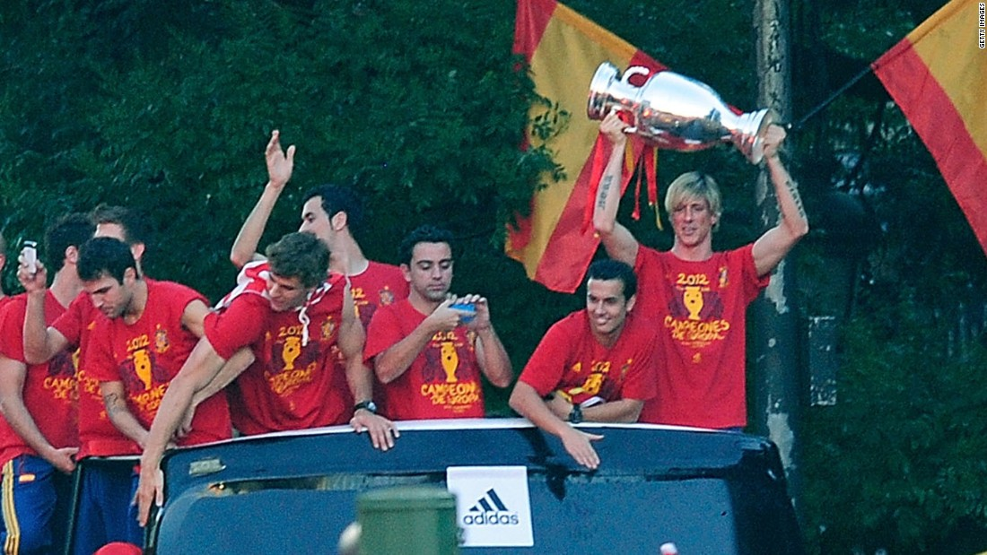 Torres holds aloft the Euro 2012 trophy during a victory parade after Spain's triumph. He scored in the final against Italy.<br />