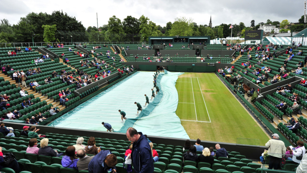 Ground staff workers remove covers from the grass before the start of the fourth round men's singles match between France's Jo-Wilfried Tsonga and Mardy Fish of the United States on Tuesday.