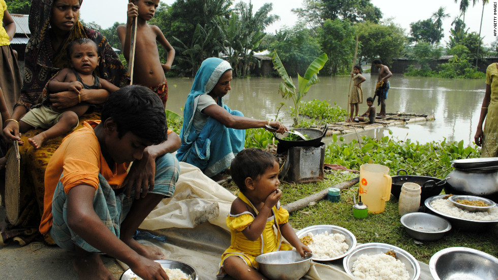 An Indian family eats by a road after their house was washed away by floodwaters at Bulut Village on June 30. The floods have left almost 2 million people homeless.