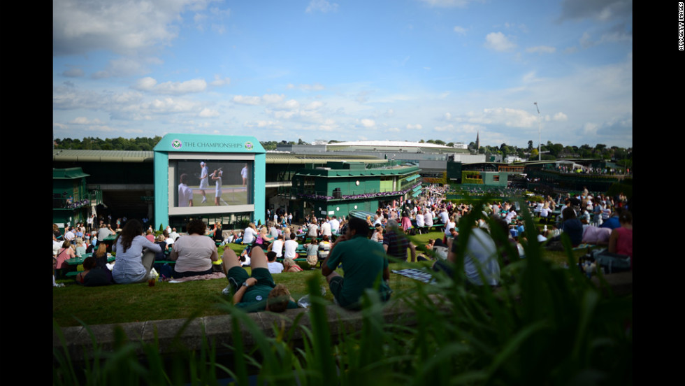 Spectators follow the day's matches on the big screen in the afternoon sun on Murray Mound on Thursday.