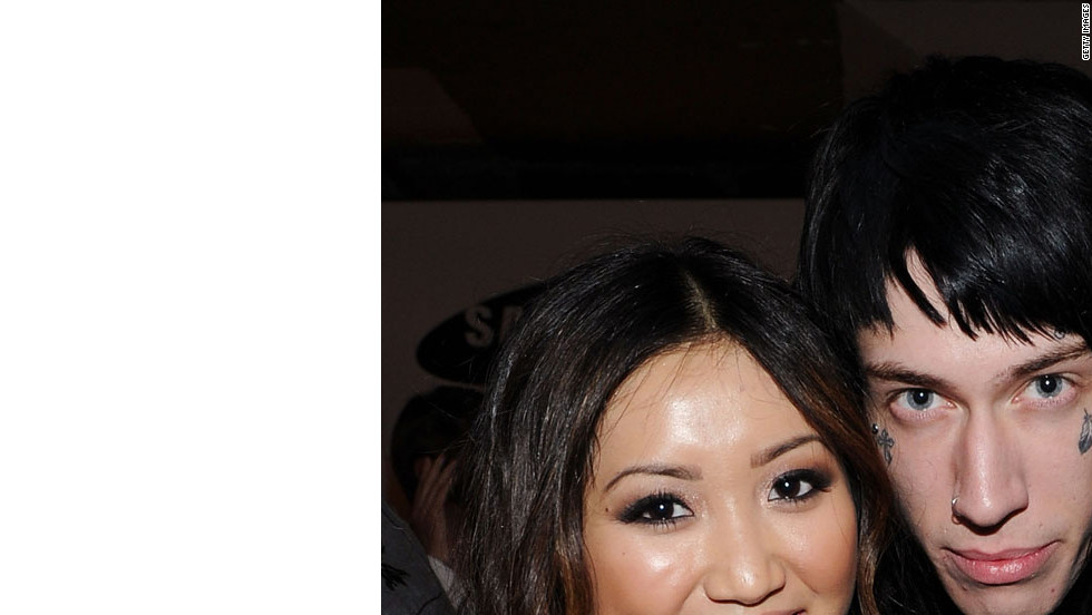 Heavily tattooed and pierced musician Trace Cyrus, singer Miley's brother, with actress Brenda Song.