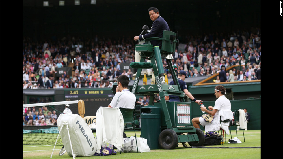 Umpire James Keothavong looks on as Novak Djokovic of Serbia and Roger Federer of Switzerland take a break during their Gentlemen's Singles semifinal match on Friday, July 6, in London, day 11 of the tournament.