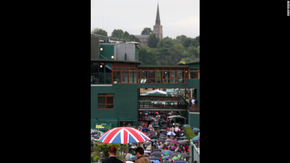 A crowd tries to shelter itself  from the rain Friday on day 11 of the Wimbledon Lawn Tennis Championships.