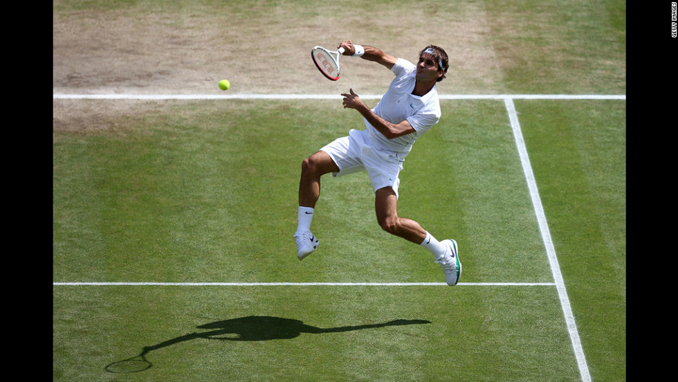 Federer jumps and returns a shot to Murray on Sunday.