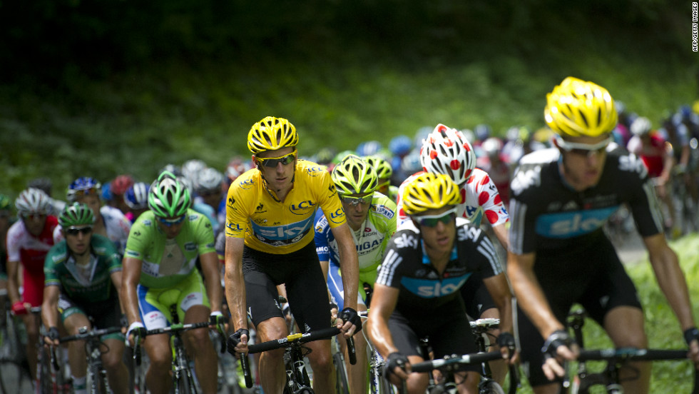 Overall leader Bradley Wiggins of Great Britain rides in the peloton with his Team Sky teammates Sunday.
