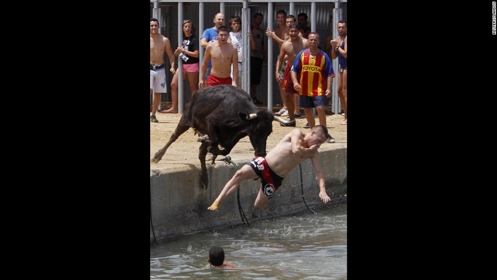 A bull chasing revelers jumps into the sea Monday during the Bous a la Mar festival in the eastern Spanish coastal town of Denia.
