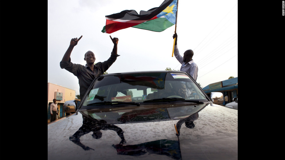 South Sudanese men drive around Juba waving the national flag Sunday on the eve of the country's first independence day.