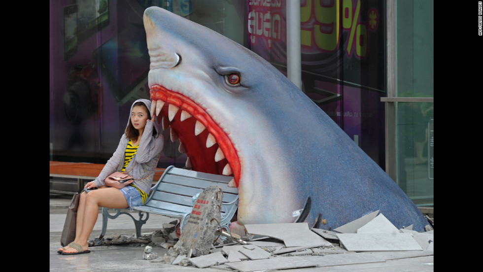 A tourist sits next to a large art display of a shark at a shopping mall in Bangkok, Thailand, on Monday.