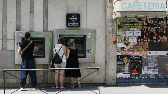 People withdraw money from cash machines adjacent to a boarded up cafeteria on July 3, 2012 in Madrid, Spain.