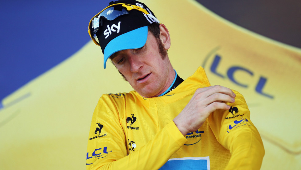 Bradley Wiggins pulls on the yellow jersey after successfully defending the maillot jaune after winning his first Tour de France stage victory in the time trial between Arc et Senans and Besancon.