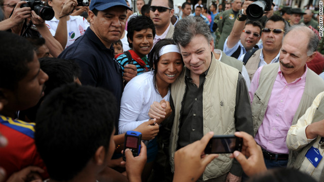 Colombian President Juan Manuel Santos has his picture taken with a resident of Toribio on July 11, 2012.