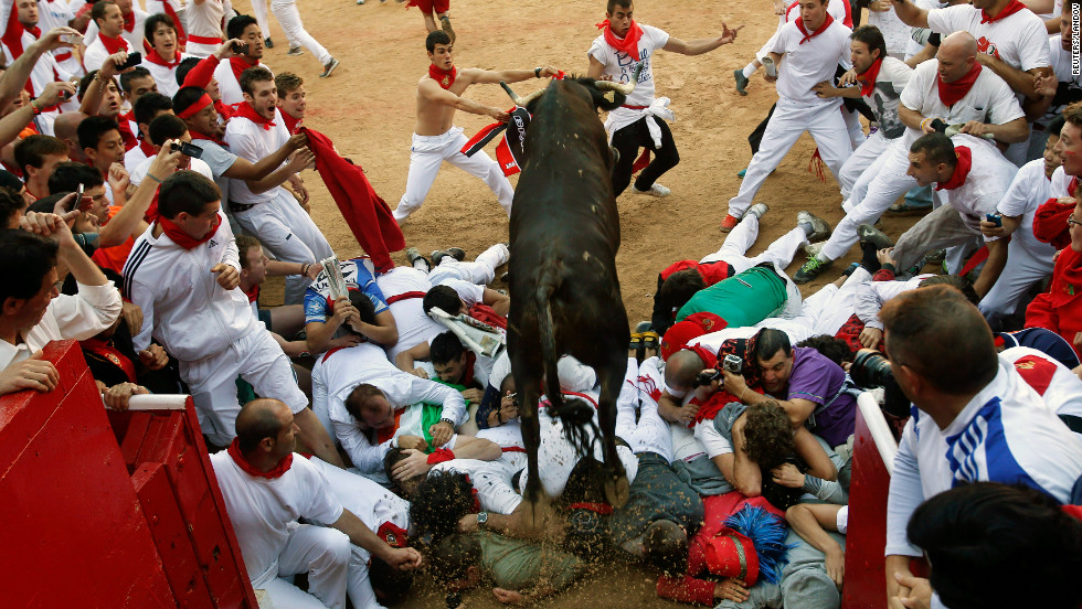 A bull jumps over revelers as others clear the way as the animals enter the bullring on Thursday.