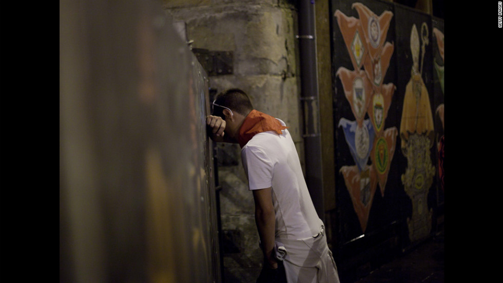 A reveler leans against the fence next to a painting of San Fermin in Curva Estafeta before Friday's running-of-the-bulls.