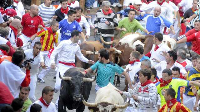 Participants run in front of Torrehendilla-Torreherberos's bulls during the last San Fermin Festival bull run, on July 14, 2012, in Pamplona, northern Spain. The festival is a symbol of Spanish culture that attracts thousands of tourists to watch the bull runs despite heavy condemnation from animal rights groups. AFP PHOTO/Pedro ARMESTRE        (Photo credit should read PEDRO ARMESTRE/AFP/GettyImages)