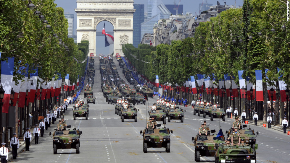Soldiers from the 92nd Infantry Regiment march down the Champs Elysees with Panhard light armoured vehicles.