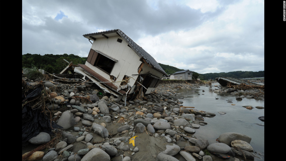 A collapsed house lies in a riverbank along the Hoshino River in Yame City, Japan, on Monday after four days of torrential rainfall. The downpours have damaged homes across the region and prompted the temporary evacuation of thousands of people.