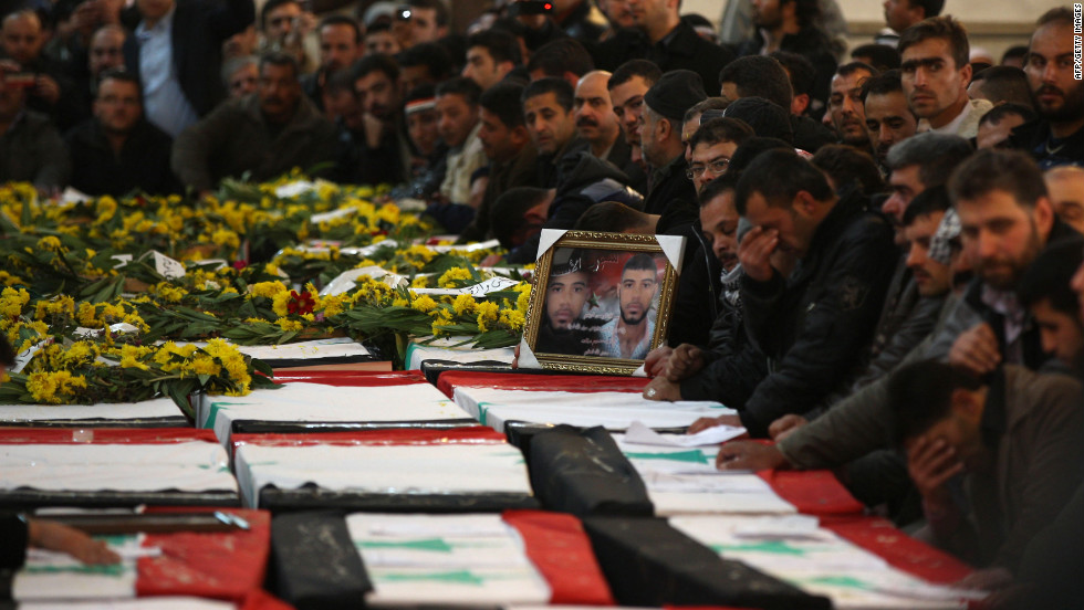 A day after the twin suicide bombings, Syrian mourners pray over the coffins of the 44 people killed during a mass funeral in Damascus.