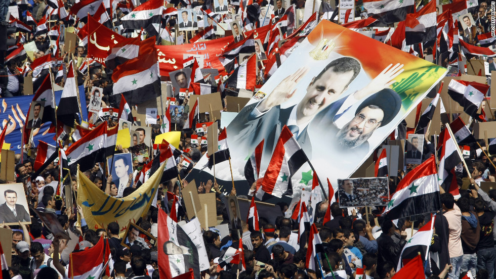 Thousands of Syrians wave their national flag and hold portraits of President Bashar al-Assad and Lebanon's Hezbollah chief Hassan Nasrallah, right, during a rally to show support for their leader on March 29, 2012 in Damascus.