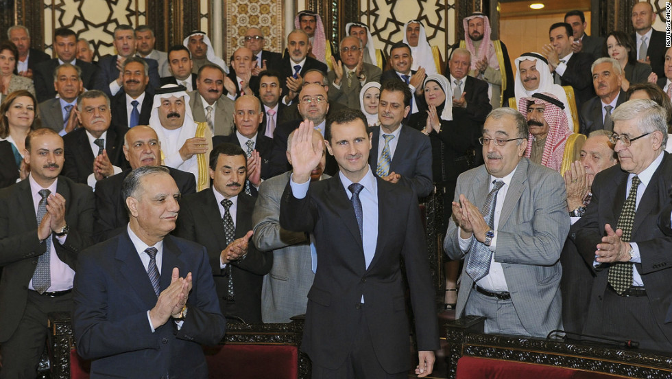 "Syria's President Bashar al-Assad waves as he arrives for a speech to Syria's parliament in Damascus on June 3, 2012. The embattled president denied that government forces were behind the ""outrageous"" massacre in Houla."