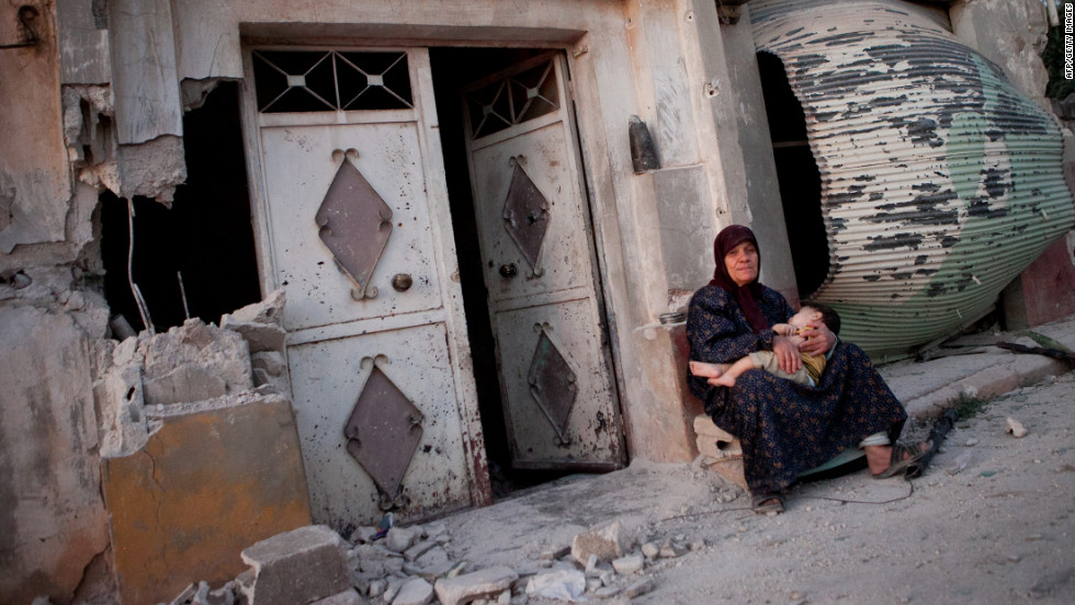 A Syrian woman sits with her grandson outside a damaged building after attacks in the Syrian village of Treimsa on July 13, 2012. More than 200 people were massacred in the town, according to activists.