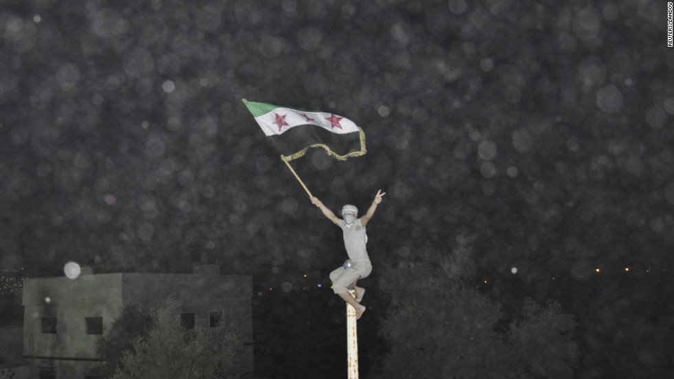 A Syrian demonstrator holds an opposition flag during a protest in Damascus on July 2, 2012. There have been increasing reports of violence in the Syrian capital.