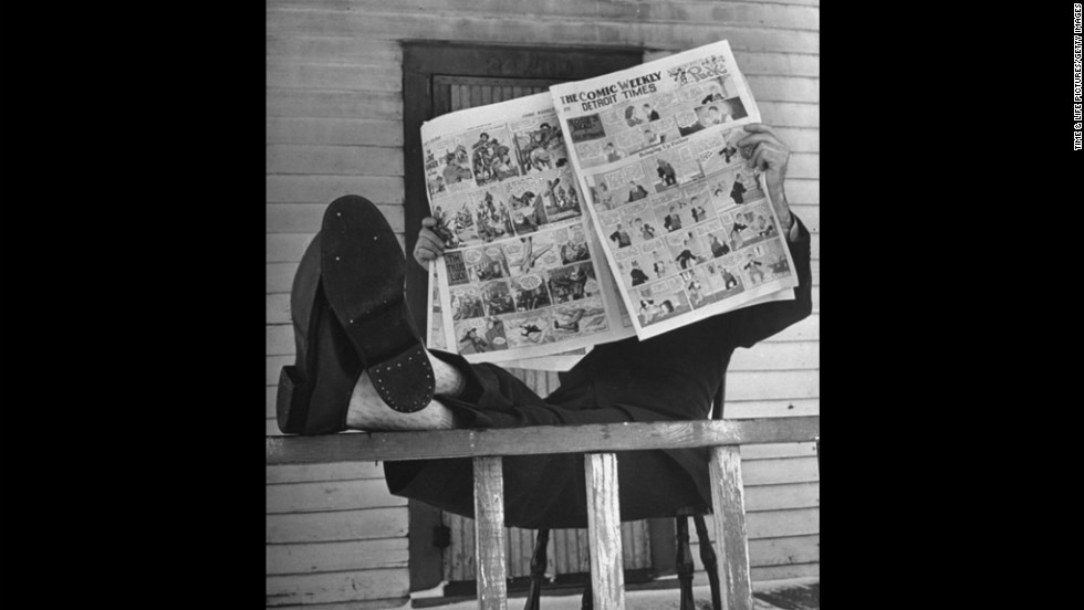 A man reads the comics section of the Detroit Times during World War II.