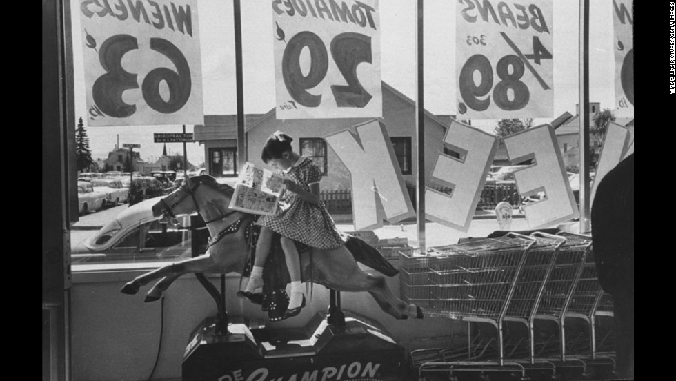 A girl sits on a mechanical horse and reads a comic book at an Anchorage, Alaska, supermarket in 1958.