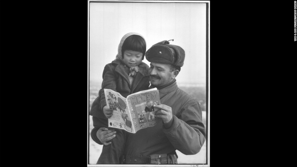 During the Korean War, a Turkish soldier holds a young girl as they glance at an American comic book in 1951.