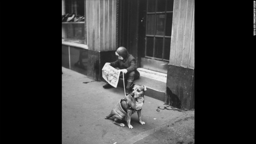 A young boy reads a comic strip on a step while his dog sits idly by in 1944.