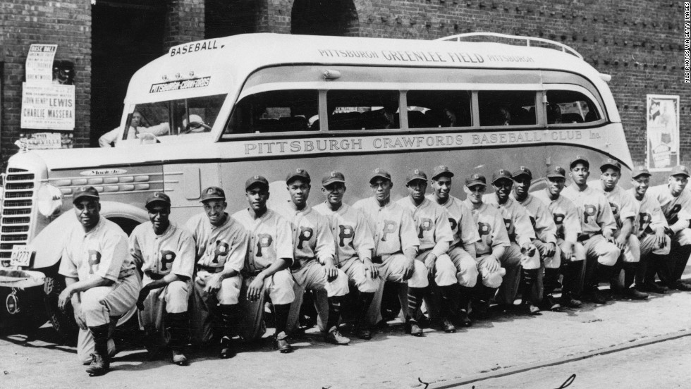 Here, the 1935 Negro Leagues Pittsburgh Crawfords pose in front of their team bus, similar to the bus the Anderson Monarchs are traveling in across the United States.