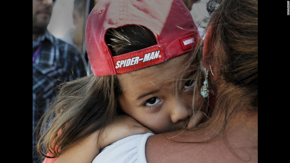 Adariah Legarreta, 4, is comforted by her grandmother Rita Abeyta near the Century 16 Theater in Aurora.