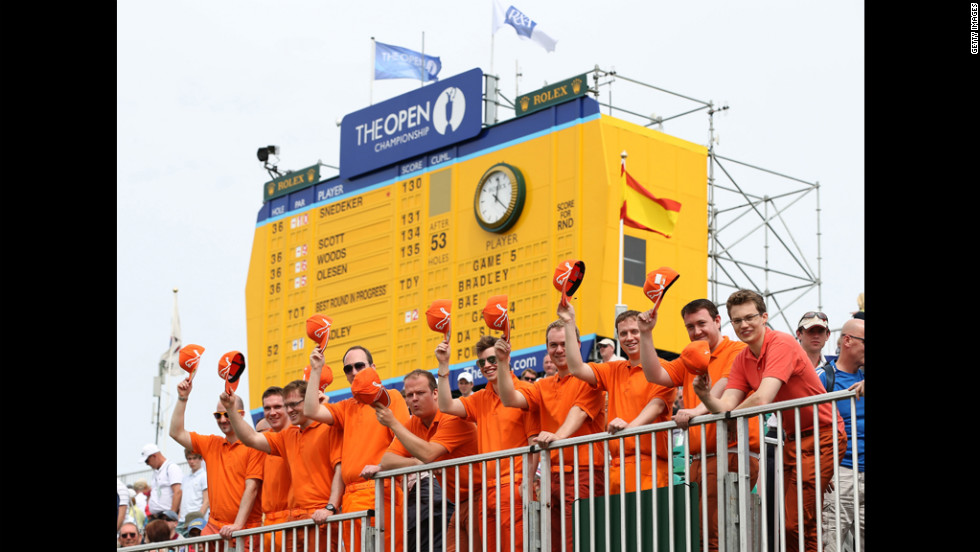 Fans of young American star Rickie Fowler fans pose in the bleachers at No. 18, dressed in their hero's customary bright, monochrome colors.