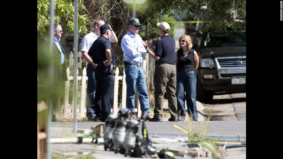 Law enforcement officers speak with Colorado Gov. John Hickenlooper, center, outside the suspect's apartment July 21, 2012.